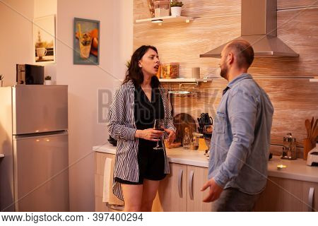 Husband And Wife Relaxing Drinking Wine In Kitchen In The Evening. Adult Couple At Home, Talking, Sm