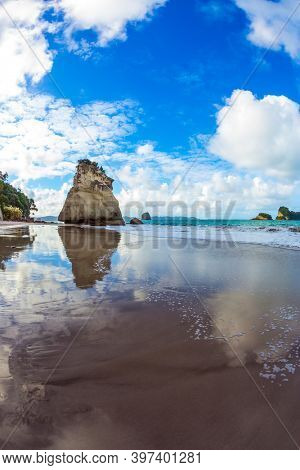 The concept of exotic, ecological and photo tourism. The far end of the earth. Travel to New Zealand. Ocean tidal wave in the Cathedral Cove. Mirror reflections of clouds in wet sand