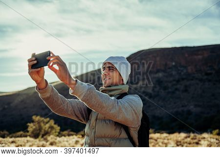 Young Caucasian Hiker Taking Selfie With Smartphone While Walking Through Luscious Mountain