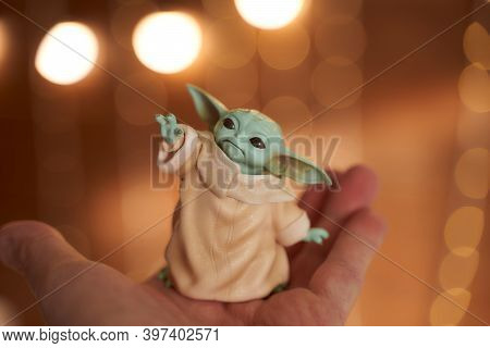 November, 2020: Display Of Baby Yoda, An Action Figures, Standing On Hand. Christmas Background Boke