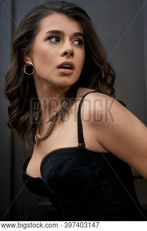 Side View Of Young Caucasian Stunning Woman Wearing Black Lace Corset And Golden Accessories Looking