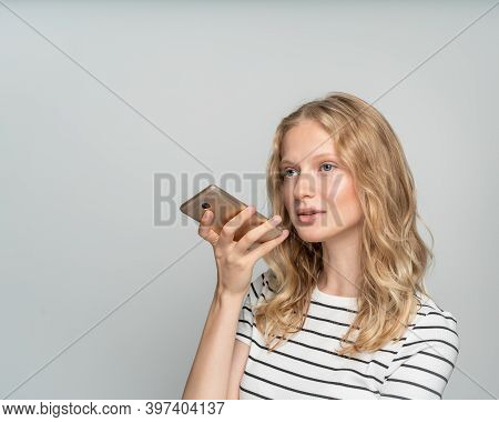 Pretty Female Dictating Voice Message On Mobile Phone Standing Near White Wall, Gray Background. Nat