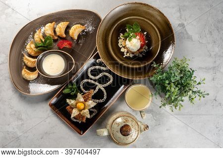 A Set Of Beautiful Desserts And A Cup Of Green Tea With A Teapot. Sweet Gyoza Dumplings With Fresh S