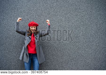 Adult Woman In Modern Casual Clothing Standing In Front Of Gray Background. She Is Ecstatic. Copy Sp