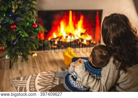 Mom And Little Son Are Sitting In An Embrace Next To The Fireplace. Concept Of Creating A Cozy Winte