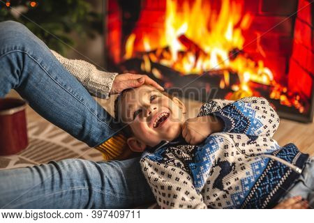 Mom And Son Are Sitting Next To The Fireplace And Having Fun. Concept Of Creating A Cozy Winter Atmo