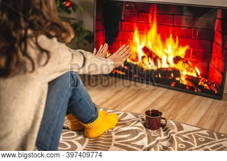 Girl In A Sweater And Socks Is Sitting Next To The Fireplace, Which Is Depicted On The Tv Screen And