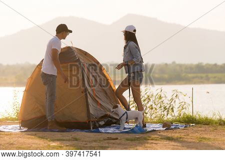 Young adult Asian couple pitch and set up tent for camping around the lake. Camping trip with dog outdoor activity campsite concept.