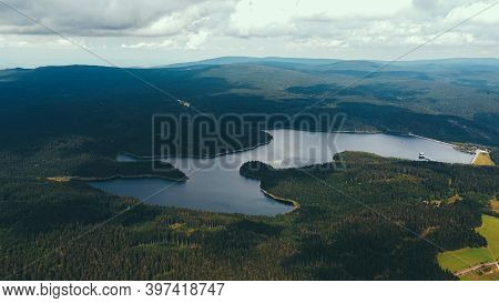 Dam Surrounded By Forests And Mountains And Clouds In The Sky