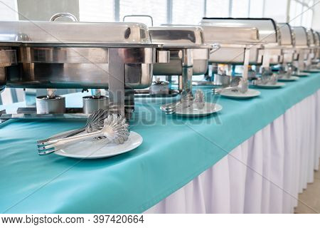 Shiny Metal Food Warmers, Stacks Of Plates And Other Kitchen Equipment On The Table For A Gourmet Ba