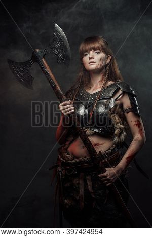 Armed With Two Handed Axe Nordic Grimy Amazon In Dark Armour With Brown Hairs Poses In Dark Backgrou