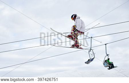 Side View Of Man Skier Making Jump With Cloudy Sky And Ski Lifts On Background. Male Freerider On Sk