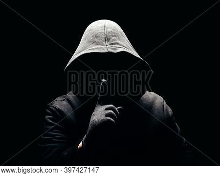 Photo Of A Scary Horror Man In Hoodie Showing Silence Hand Sign In Dark.