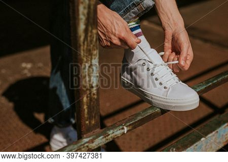 Model hands fixing laces on a white sneaker