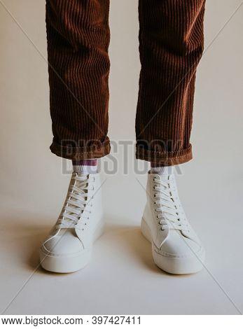 White high top sneakers on corduroy pants model