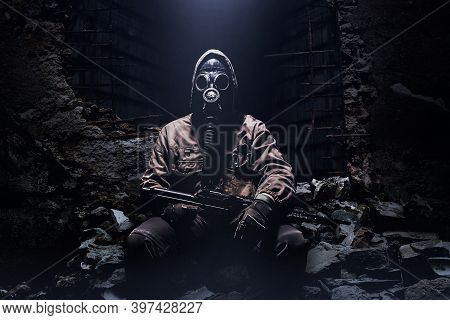Photo Of A Stalker Warrior With Rifle And Soviet Protective Rubber Gas Mask Sitting On Ruins On Dark