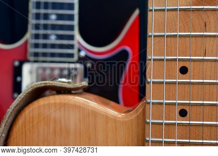 Electric Guitar Background. Maple Fretboard, Strings And Swamp Ash Body Close-up.
