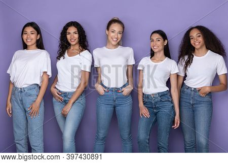 Multiethnic Group Of Cheerful Women Posing Standing Together And Smiling To Camera Over Purple Studi