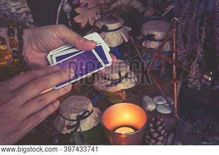 Woman Hand Is Holding Deck Of Tarot Or Oracle Cards Performing Fortunetelling. Toned To Cold Colors