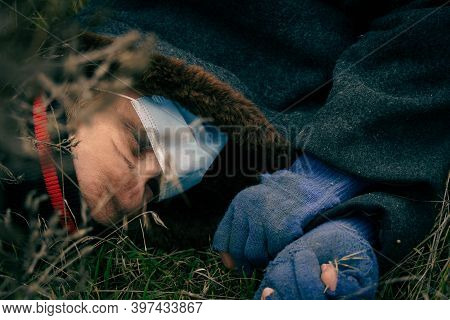 Poor Dirty Man Lies Dead On The Ground A Homeless Man In A Medical Mask Lies On The Wet Ground Uncon