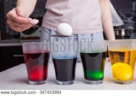 Coloring Easter Eggs At Home Using Spoon In Women's Hands Dipped In Concentrated Food Coloring Diffe