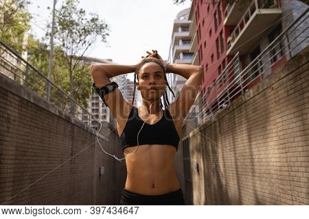 Front view of thoughtful young Mixed race woman tying her updo in the city