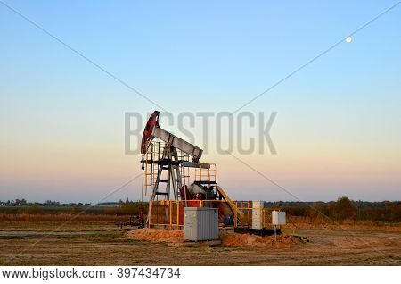 Oil Drill Rig And Pump Jack On Sunset Background. Oil Drilling Derricks At Desert Oilfield For Fossi