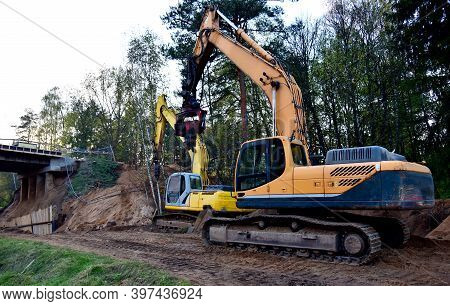 Excavator With Drilling Attachments At Construction Site. Rock Drill Equipment And Vibroflotation Pr