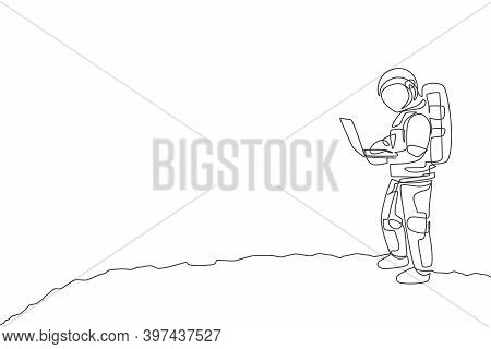 One Continuous Line Drawing Of Young Spaceman On Spacesuit Standing While Typing In Moon Surface. As