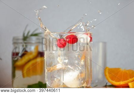 A Piece Of Ice Falls Into A Glass, Splashes Cranberry Cocktail With Ice And Mint Detox Water With Or