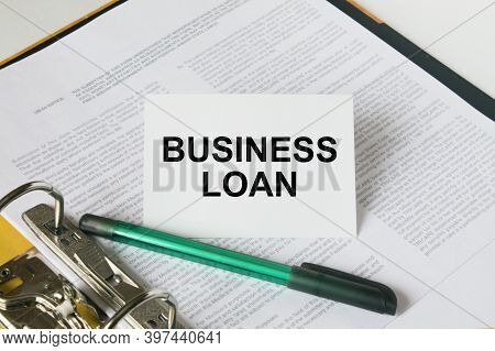 Text Business Loan On A White Card That Is In A Folder With Documents And A Green Pen