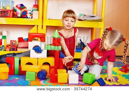 Little girl playing block and construction set in preschool.