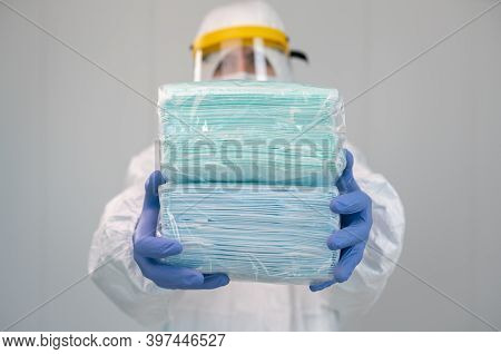 Doctor In Ppe And Medical Mask Shows Packing Of New Surgical Masks. Covid-19
