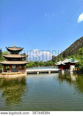 Traditional Chinese Pavilions With The Snowy Jade Dragon Mountain In The Background, Lijian, China