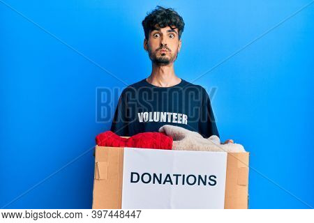 Young hispanic man holding donation box with clothes puffing cheeks with funny face. mouth inflated with air, catching air.