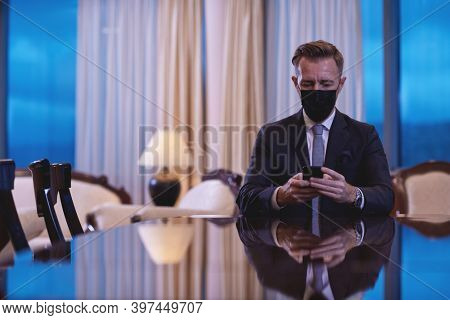 business man using smart phone at luxury office wearing face mask