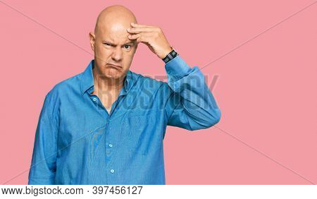 Middle age bald man wearing casual clothes worried and stressed about a problem with hand on forehead, nervous and anxious for crisis