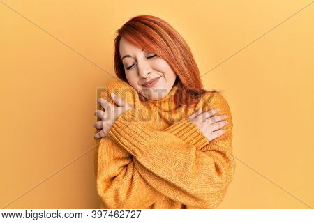 Beautiful redhead woman wearing casual winter sweater over yellow background hugging oneself happy and positive, smiling confident. self love and self care