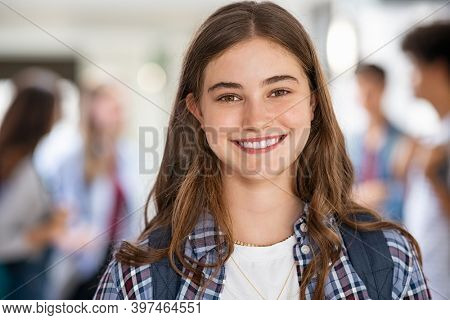 Portrait of beautiful girl standing in college campus and looking at camera. University young woman with backpack smiling. Satisfied and proud student girl standing in high school hallway.
