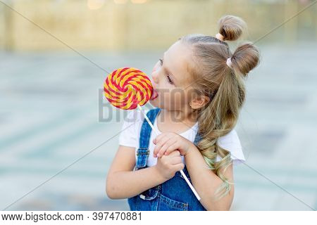 Portrait Of A Child Girl With A Large Lollipop In The Summer On The Street
