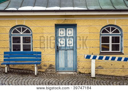 Yellow House With Blue Bench