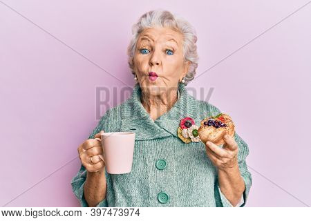 Senior grey-haired woman drinking a cup of coffee and eating bun making fish face with mouth and squinting eyes, crazy and comical.