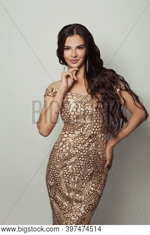 Perfect Brunette Model Woman With Long Curly Hair Wearing Gold Evening Gown Posing On White Backgrou