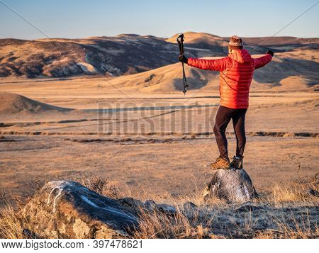 happy male hiker with trekking post at foothills of  Rocky Mountains in northern Colorado - fall scenery at sunrise in Soapstone Prairie Natural Area near Fort Collins