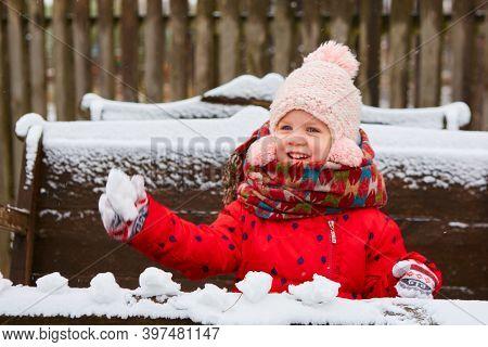 Playful Girl Has A Fun Winter Time In A Snow Park. Cute Playful Girl Outdoor Enjoying First Snow.
