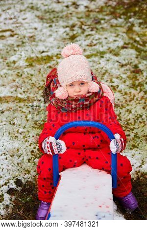 Winter Outdoor Portrait Of Adorable Dreamy Baby Girl In Knitted Hat And Scarf