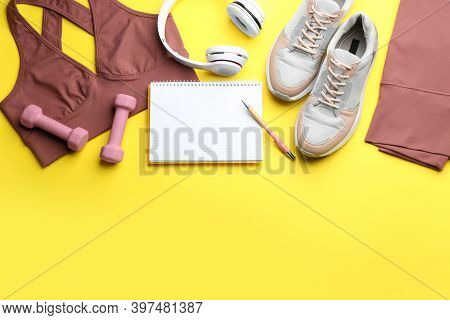 Flat Lay Composition With Sportswear, Notebook And Dumbbells On Yellow Background, Space For Text. G