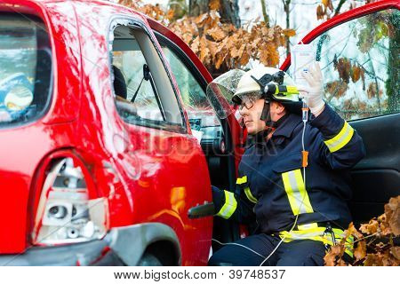 Accident - Fire brigade rescues accident Victim of a car, firefighter holds a drip for Infusion poster