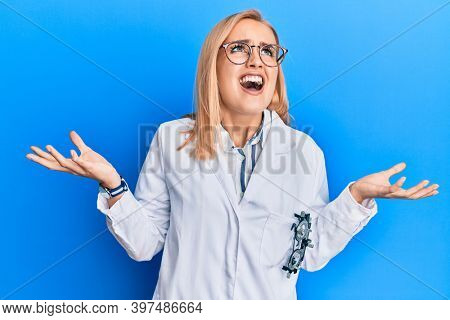 Beautiful caucasian oculist woman wearing robe and optometry glasses crazy and mad shouting and yelling with aggressive expression and arms raised. frustration concept.