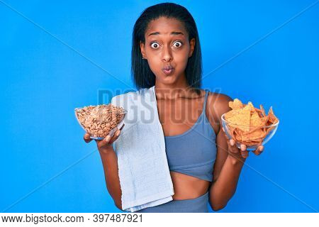 Young african american woman wearing sportswear holding nachos and cereal puffing cheeks with funny face. mouth inflated with air, catching air.